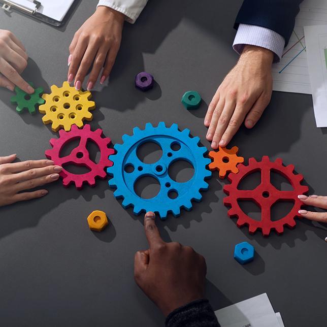 Teamwork - Business people manipulating gears on a desk